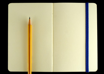 Classic opened moleskine note book with pencil