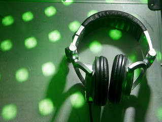 Dj headphones on party background