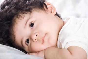 baby boy lying on bed