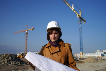 Pretty woman architect holding blueprints and standing in the bu