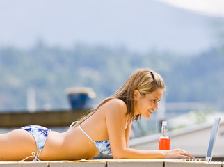 Woman laying on pier typing on laptop