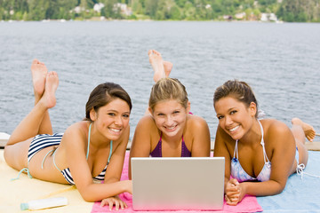 Friends laying on pier using laptop