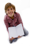 front view of boy sitting on books and reading book