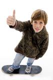 top view of boy riding skate and showing thumbs up