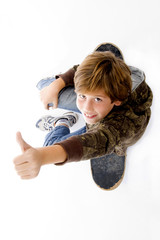 top view of boy sitting on skate and showing thumbs up