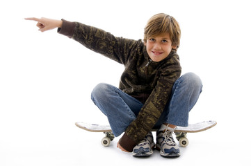 front view of boy sitting on skate and pointing
