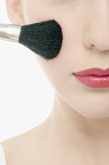 Young Woman face with Make-Up, holding  a brush in front of her, close-up (studio)