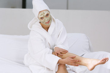 Young woman with beauty mask on her face, massaging her leg