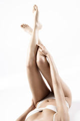Woman in lingerie lying on floor, legs in the air, close up (studio)