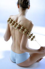 Naked woman with panties, using wooden massager on her back