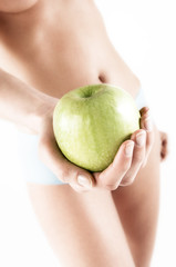 Naked woman in panties, holding a green apple, close up (studio)