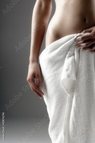 Naked woman, hand on towel on her sex, close up (studio)