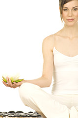 Young woman sitting in profile, yoga attitude, water lily in her hand