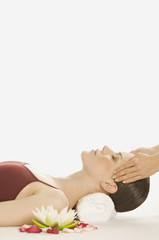 Woman having head massaged, water lily