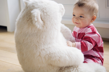 Baby playing with teddy bear
