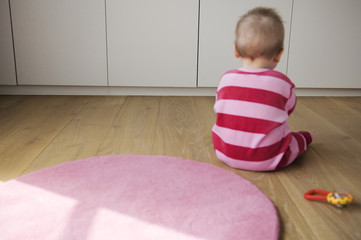 Baby playing siiting on the floor, view from the back