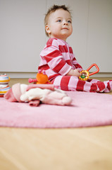 Baby playing, sitting on the floor