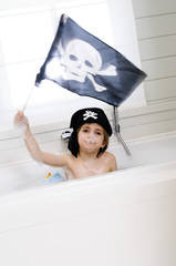 Little boy in bath holding pirate flag