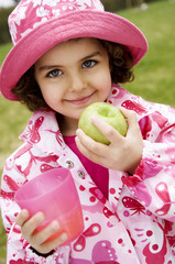 Little girl with apple and glass
