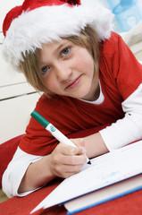 Boy disguised as Santa Claus, writing
