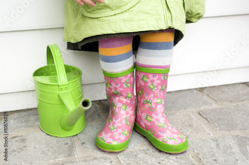 Little girl in boots, close-up, green watering can