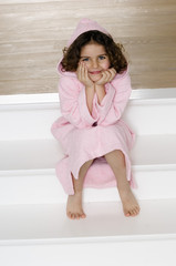Little girl sitting on stairs, with bathrobe