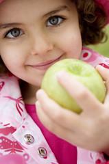 Little girl holding an apple, close-up