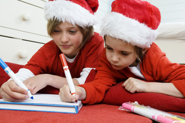 2 boys disguised as Santa Claus, writing