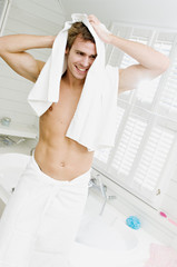 Smiling man wrapped in a towel, standing in bathroom towelling hair
