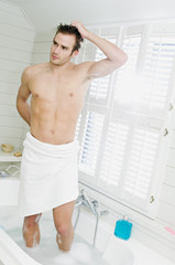 Young man wrapped in a towel standing in bath