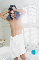 Young man wrapped in a towel, standing in bath towelling hair, smiling for the camera