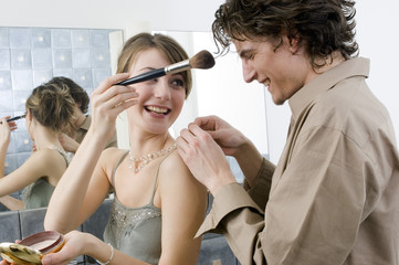 Smiling couple in the bathroom, woman holding make-up brush, man fastening her necklace