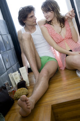 Young couple sitting on tub edge, looking at each other