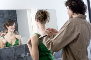 Man helping woman get dressed in front of bathroom mirror
