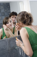 Woman applying mascara in front of bathroom mirror, man in background