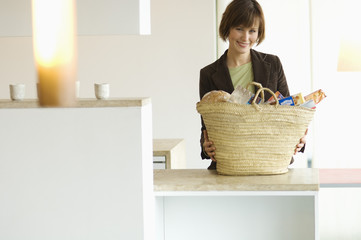 Young smiling woman with shopping basket in the kitchen
