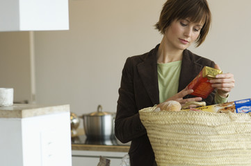 Young woman emptying shopping basket in the kitchen