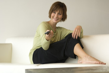 Smiling woman sitting on a sofa using remote-control