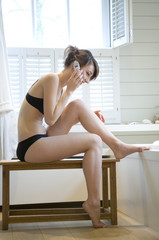 Young woman in black underwear using mobile phone, sitting on a bench in bathroom