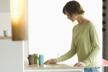 Young woman cleaning kitchen work-top