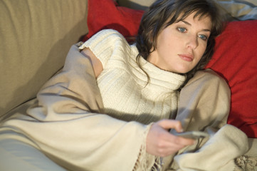 Young woman wrapped in blanket, lying on a sofa, using remote-control