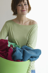 Young woman holding clothes basket