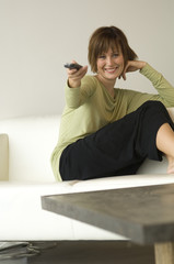 Young smiling woman sitting on a sofa using remote-control