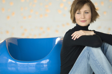 Young woman sitting on the floor, leaning against blue armchair