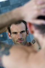Tattooed man, barechested, looking in bathroom mirror