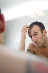Tattooed man, barechested, looking in bathroom mirror
