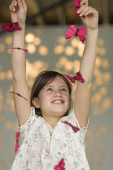 Smiling little girl playing with butterfly garland