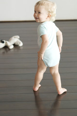 Little boy walking on wooden floor, rear view