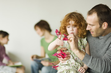Man and little girl playing with butterfly garland, woman and child in the background