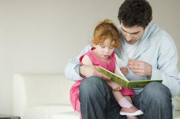 Man and little girl reading children's book